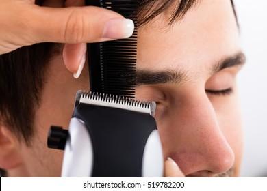 Close-up Of A Hairdresser Cutting Man's Hair At Salon