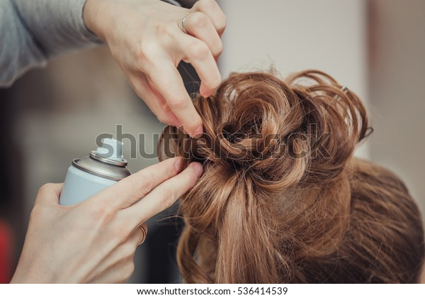 Closeup of hairdresser hands using hairspray styling on woman's healthy golden hair at barber salon