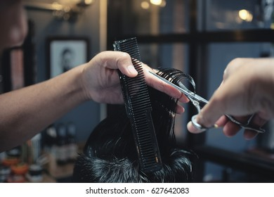 Closeup Hairdresser makes hairstyle a man with vintage tone.
