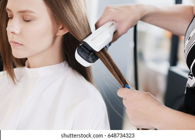 Closeup hairdresser makes hairstyle for young woman in beauty salon
