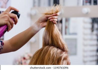Closeup of hairdresser making modern hairstyle using spray