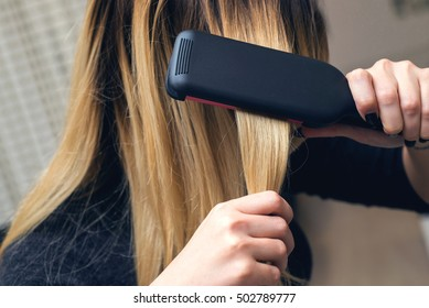 Close-up of a hairdresser straightening long brown hair with hair irons