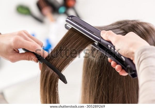 長い茶色の毛を伸ばすヘアアイロンと美容師の接写。