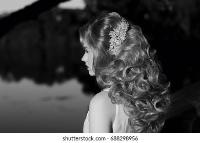 Closeup of hairstyle with barrette or bobby pin in girls hair. Golden hair woman at sunset in park.