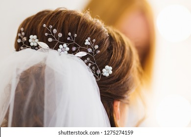 close-up hairstyle of the bride and bridal veil. in the hair ornaments with beads