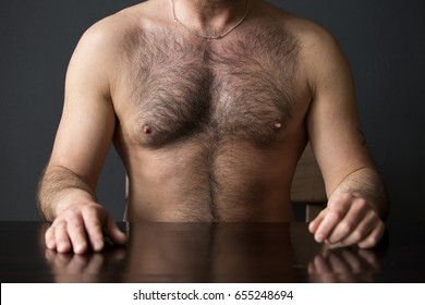 closeup of hairy chest of man sitting at table