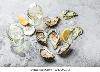 Close-up of half dozen of fresh opened oysters and shells with lemon wedges, two glasses of white wine or champagne, top view, grey rustic concrete background. Romantic or celebration with oysters