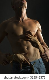 Closeup of half dressed sexual man with beautiful wet muscular body and female hands touching male six-pack and belly standing in studio on black background, vertical picture