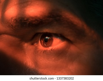 Close-up of half face of man with disturbing eyes look under red light. Psycho, scary, evil and mental disorder  concept.