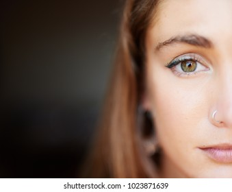 Close-up of half-face of beautiful woman with make up and nose piercing looking at camera. Copyspace.