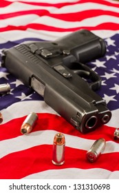 closeup of a hallow point bullet with a gun and an American flag fading to a shallow depth of field