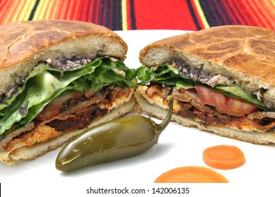 Closeup of halved Mexican torta sandwich with toasted bun and jalapeno pepper on plate over colorful tablecloth