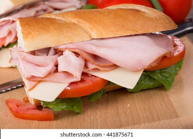 Closeup of a ham sub sandwich with cheese, tomato and lettuce on a baguette