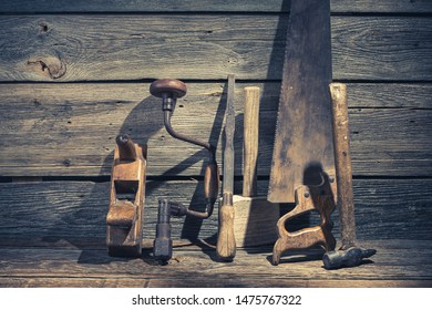 Closeup of hammer, saw and chisel in rustic workbench
