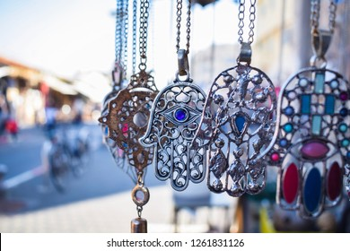 Close-up of Hamsa, also known as Fatima Hand or Hand of God necklace,  pending on a flea market in Tel Aviv-Jaffa, Israel. Metal protection amulet.