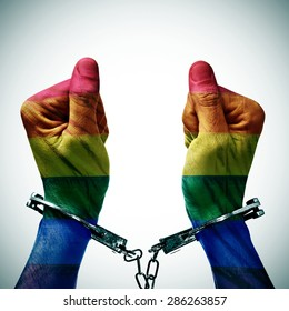 closeup of the hancduffed hands of a young man patterned as the gay pride flag, to denounce the criminalization of homosexuality in some countries