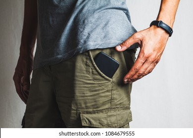 close-up of a hand about to take a ringing phone from a pant pocket
