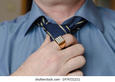 A close-up of a hand adjusting a blue and yellow striped tie around his neck. A middle-aged man with a gold ring on his index finger. Lifestyle. Indoor.