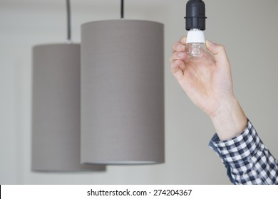 Closeup of hand adjusting electric bulb by pendant lights at home