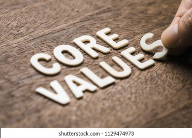 Closeup hand arrange wood letters as CORE VALUES word