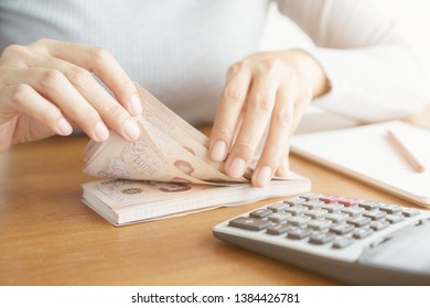 Close-up hand of asian woman using calculator counting and count money in home.