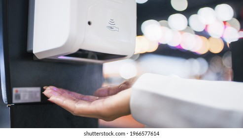 Close-up hand of Asian woman using hand sanitizer or alcohol gel dispenser, rubbing hand in public place. Clean healthy lifestyle, coronavirus prevention concept