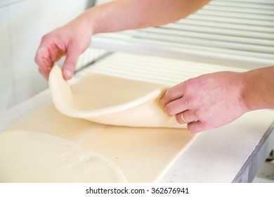 Close-up the hand of a baker kneading and shaping dough