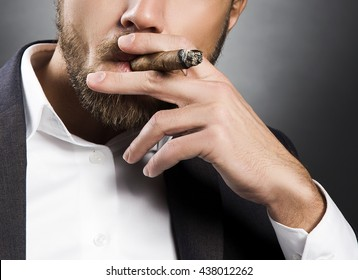 Close-up hand of bearded caucasian man smoking a cigar. Wearing grey suit and white shirt. Studio portrait on gradient black to grey background.