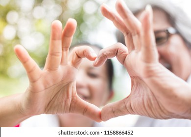 closeup hand and blur face on nature background, Asian senior people show heart sign with hand, they feeling happy and smiling, retirement happiness