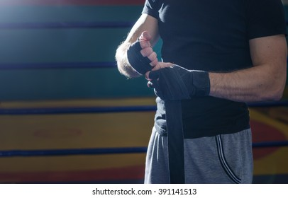Close-up of hand of boxer who pulls wrist wraps before the fight or training.