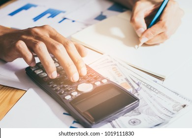 Close-up. Hand of  business or account working calculator, profit or graph economy on home office tables, instagram style filter photo vintage tone