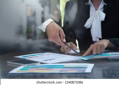 Closeup of Hand of business man and spreadsheet graph papers on Table. Audit Tax return on investment analysis Shareholders and Capital Market. Auditor and analytics concepts