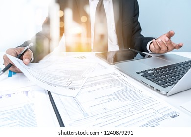 Closeup of Hand of Business MAN and SPreadsheet graph papers on table. Business Investment Advisory Team Analyzes company's Annual financial statements.Audit tax return analysis concepts