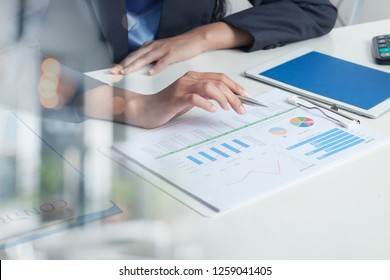 Closeup of Hand of Business Woman Hold pen and Spreadsheet graph Papers on Table.AUDIT tax Return on investment Analysis Shareholders and Capital Market. Auditor and Analytics concepts