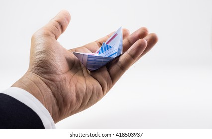 Closeup of hand businessman holding boat paper graph.Business goal concept