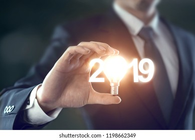 Closeup hand of businessman holding light bulb and number 2019 year, Business idea new year concept.