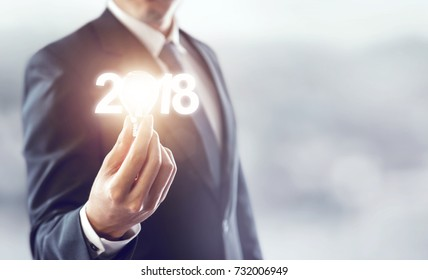Closeup hand of businessman holding light bulb and number 2018 year, Business idea new year concept. copy space.