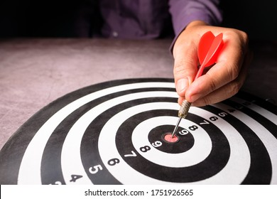 Closeup hand of businessman take a red dart hit on the center of dartboard, goal setting, target your customer, or marketing plan concept
