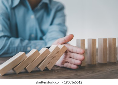 close-up hand The hand of a businessman who is stopping or preventing a falling block.Risk protection concept,Eliminating the risk
