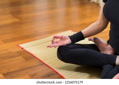 Closeup of Hand of Caucasian Brunette Woman Practicing Yoga Indoors. Doing Sukhasana Exercises In Lotus Pose. In Front of Sunny Window in Background.Horizontal Image Composition