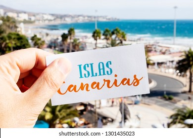 closeup of the hand of a caucasian man holding a signboard with the text Islas Canarias, Canary Islands written in Spanish, at Playa del Ingles, in Maspalomas, Gran Canaria, Spain