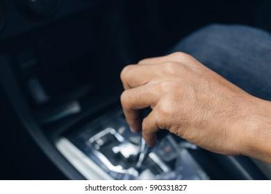 Closeup hand change gear while driving car