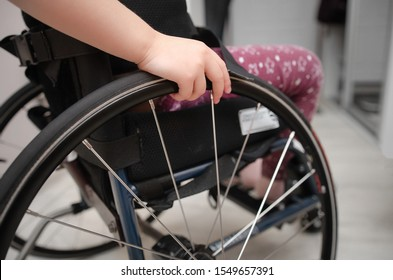 close-up hand of a child on a wheel from a wheelchair. Disabled children concept.