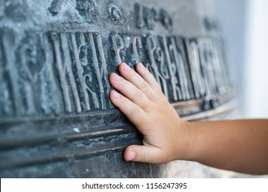 Close-up. The hand of the child touches a large church bell with ancient Slavic inscriptions. The concept of spirituality. Russia. Rostov the Great.