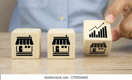 Close-up hand choose graph icon on cube wooden toy blocks place in line up with franchise business store icon. for small business growth and  branch expansion strategy of financial marketing planning.