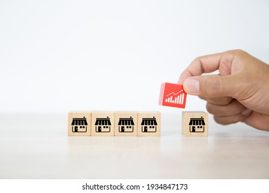 Close-up hand choose graph icon on cube wooden toy block stacked with franchise business store icon for business growth and branch expansion and bank loan.