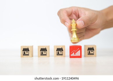 Close-up hand choose king chess on cube wooden toy blocks stacked with graph and franchise business store for business growth and  branch expansion strategy of financial marketing planning concepts.
