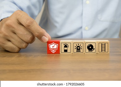 Close-up hand choose prevent icon on cube wooden toy blocks stacked with fire exit prevention icon for fire safety protection concepts. - Shutterstock ID 1792026605