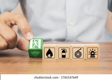 Close-up hand choose a wooden toy blocks stacked in pyramid with fire exit icon for fire safety protection concepts.