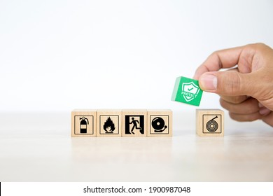 Close-up hand choose wooden toy blocks stacked with fire protect icon with fire extinguisher and door exit sing symbol for safety prevent and protection is accident concepts.